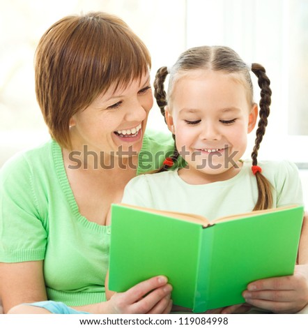 Mother is reading book for her daughter, indoor shoot - stock photo