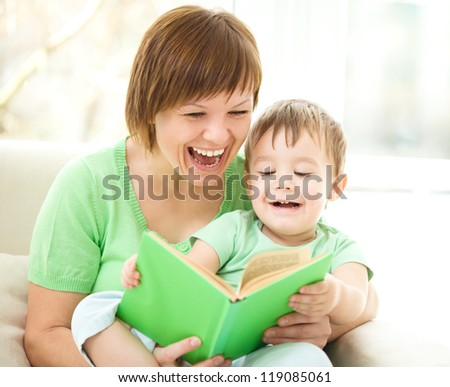 Mother is reading book for her son, indoor shoot