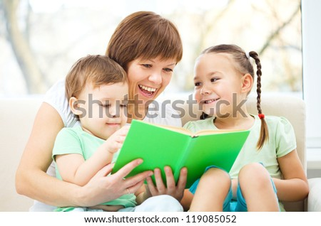 Mother is reading book for her two children, indoor shoot - stock photo