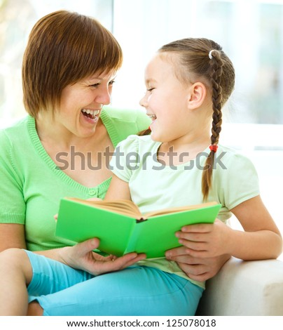 Mother is reading book with her daughter, indoor shoot - stock photo