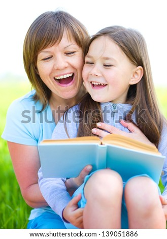 Mother is reading book with her daughter, outdoor shoot - stock photo