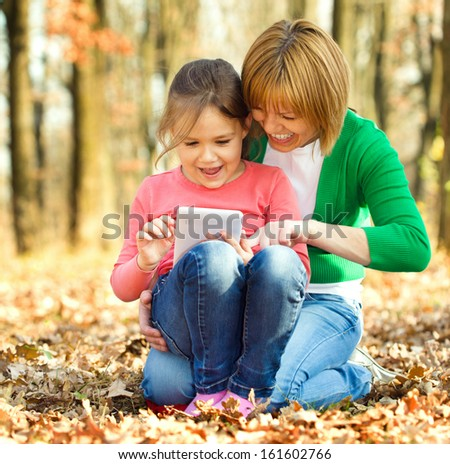 Mother is reading from tablet with her daughter, outdoor shoot
