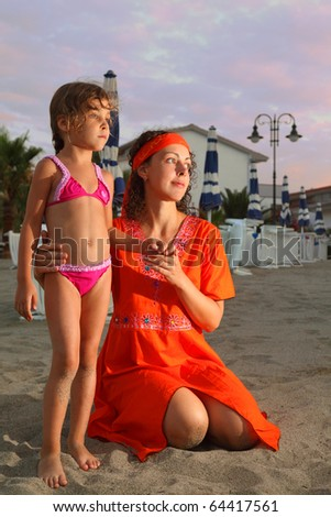 mother is sitting on beach in evening. little daughter standing nearly. Mom wore a red dress