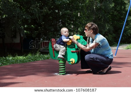 Mother is swinging her son on wooden horse