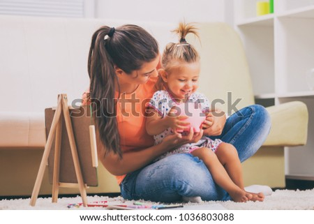 Mother is teaching her daughter how to save money.