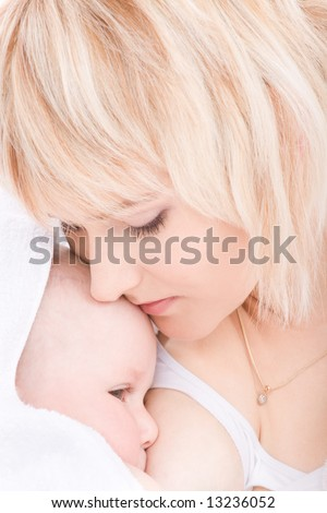 Mother kiss and breast feeding her baby girl