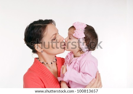 Mother kisses her little daughter on a white background