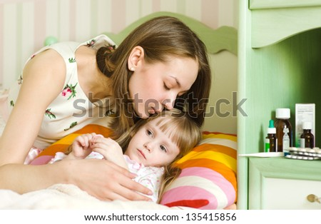 mother kisses the sick child