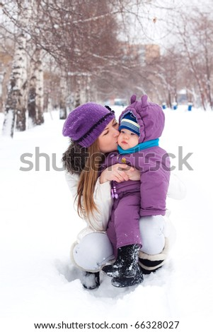 mother kissing and holding a baby, snow, winter park, walk