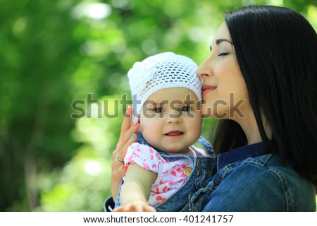 bb612542486 Mother kissing and holding small daughter baby girl cute hazel-eyed kid  tiny little child