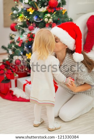 Mother kissing baby near Christmas tree
