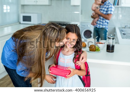 Mother kissing girl holding school lunch box with family in background at home