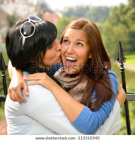 Mother kissing her daughter happy embrace outdoors teen leisure loving