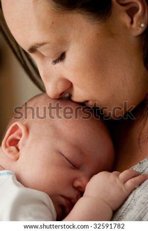 Mother kissing her newborn while he sleeps.