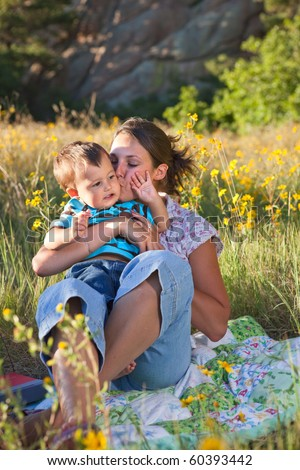 Mother kissing her son, sitting on a blanket in middle of wildflowers