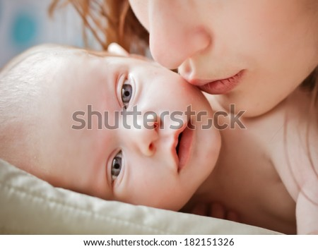 MOther kissing little baby . Baby laying on the pillow