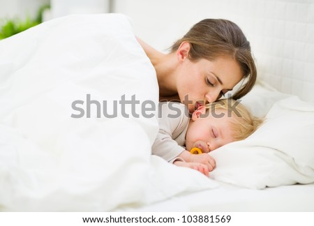 Mother kissing sleeping baby