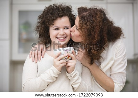 Mother kissing teenage girl holding cup, smiling
