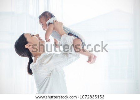 Mother lifting and playing with newborn baby, baby talking to mother. Health care family love together mother's day concept