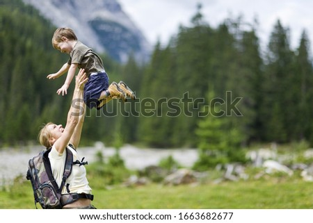 Mother lifting boy up in countryside