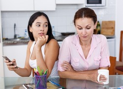 Mother looking into smartphone her young daughter in kitchen