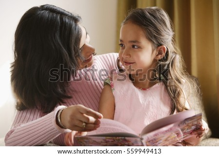 mother looks at daughter sitting on her lap