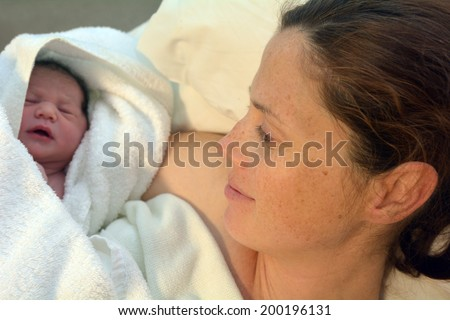 Mother looks at her newborn baby in bed immediately after a natural water birth labour. Concept photo of  pregnant woman, newborn, baby, pregnancy.