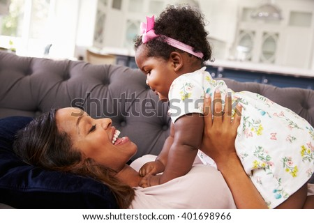 Mother lying back holding her toddler daughter on top of her