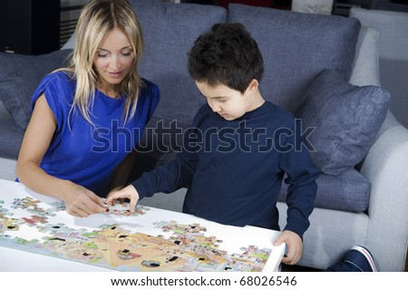 mother making a puzzle together with  her son