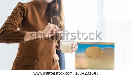 Mother making baby formula in milk bottle for a newborn baby feed.Woman holding spoon preparing baby formula milk powder for her child at table with milk box.Healthy Healthcare child development.