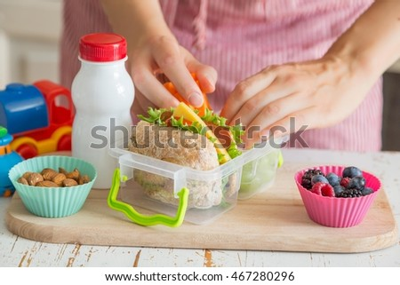 Mother making school lunch in the kitchen