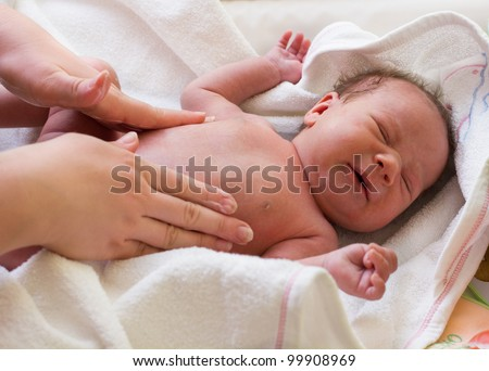 Mother massaged crying baby with colic