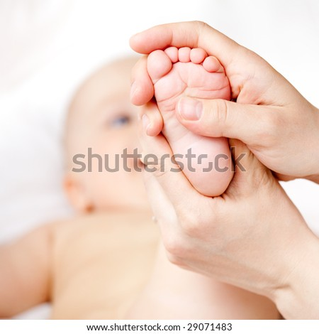 Mother massaging her child's foot shallow focus