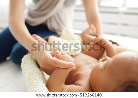 Mother massaging her newborn baby, close-up. Gymnastic, physical training, strengthening exercises for babies, early development, healthcare concept