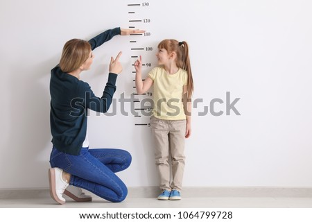 Mother measuring height of her daughter near white wall