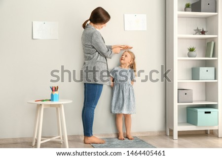 Mother measuring height of little girl near wall