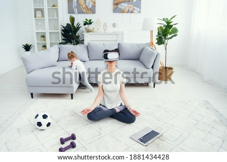 Mother meditating in lotus yoga position uses vr goggles while her daughter watches cartoons on background. Top view