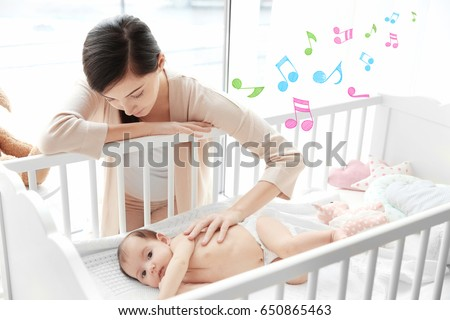 Mother near baby lying in cradle. Lullaby songs and music concept