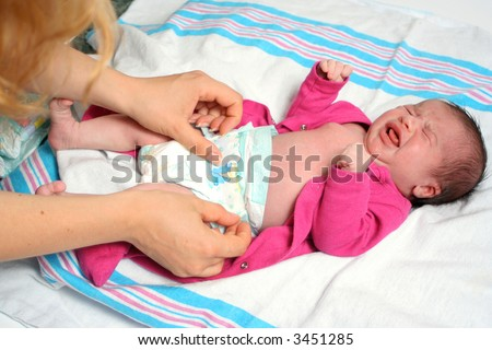 mother of a newborn baby girl changing diaper, while baby is not very happy!!