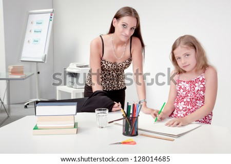 Mother or teacher supervising a pretty little girl as she sits at a table with a large sketch book drawing, interior portrait in an office or classroom
