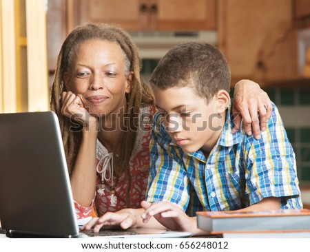 Mother overlooks as her teenaged son uses his laptop to study in their kitchen