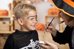Mother painting face of her son for Halloween celebration