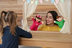Mother performing puppet show for her daughter at home
