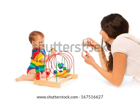 Mother photograph her little toddler boy playing with puzzle developing toy with camera on cell phone
