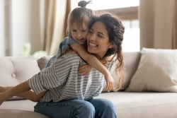 Mother piggybacks her little preschool cute daughter seated on couch enjoy funny active playtime together at home. Kid girl play with baby sitter in living room hug her from behind laughing having fun