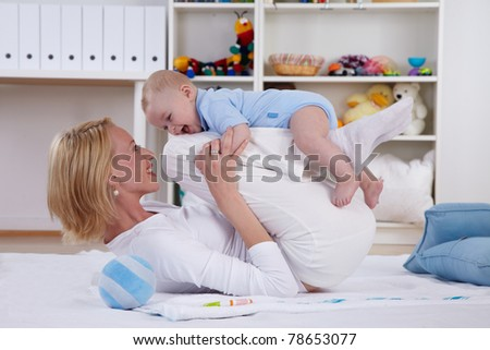 mother play on floor with her baby - stock photo