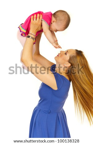 Mother playing baby girl and raising her daughter in motion isolated on white background