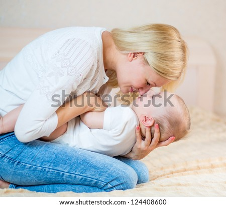 mother playing with baby boy indoors