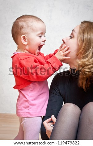 Mother playing with baby daughter