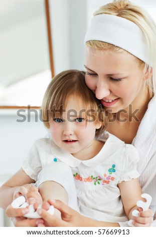 Mother playing with her cute daughter in the bathroom